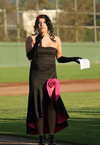 A player dressed in an evening gown stands in the field
