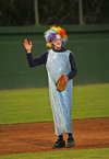 A player in a dress and a multi-colored clown wig waves