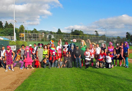 Participants and ball players dressed in costume take a group photo on the baseball field